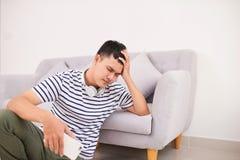 Rozpaczający młodego człowieka obsiadanie na podłogowym mienia smartphone obrazy stock