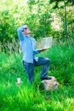 Młody człowiek outdoors z laptopem i filiżanką zdjęcia royalty free