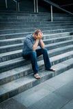 Rozpaczający młody człowiek zakrywa jego twarz z rękami siedzi na schodkach Zdjęcia Royalty Free