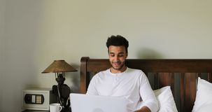Rozpamiętywający mężczyzna Używa laptopu obsiadanie Na Łóżkowym Latynoskim faceta typ Gawędzi Online W sypialnia ranku zbiory