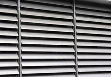 Rozpieczętowana kruszcowa nadokienna żaluzja przy budynkiem biurowym zdjęcie stock