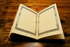 Rozpieczętowana książka na połówce, kłaść puszek ciemnego brązu drewniany stół fotografia royalty free