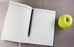 Rozpieczętowana zawiadomienie książka z zielonym jabłkiem Zdjęcie Stock