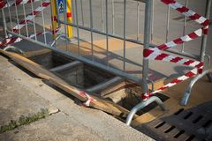 Rozpieczętowani Manholes w ulicie i Rozgraniczający R Czerwonym i Białym zdjęcia stock