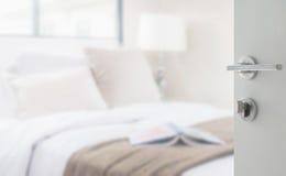 Rozpieczętowany biały drzwi sypialnia z czytelniczą lampą i książką Zdjęcie Stock