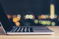 Rozpieczętowany laptop na drewnianym stole przy nocą fotografia stock