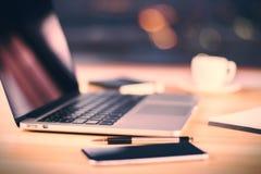 Rozpieczętowany laptop, telefon komórkowy, filiżanka kawy i pióro na drewnianym stole, fotografia stock