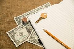Rozpieczętowany notatnik, ołówek, klucz i pieniądze na starej tkance, Obrazy Royalty Free