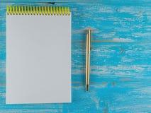 Rozpieczętowany notatnik z złocistym piórem na błękitnym drewnianym wieśniaka stole najlepszy widok Zdjęcia Royalty Free