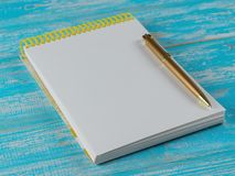 Rozpieczętowany notatnik z złocistym piórem na błękitnym stole najlepszy widok Fotografia Stock