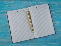 Rozpieczętowany notatnik z złocistym piórem na stole najlepszy widok Obraz Stock