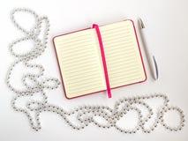 Rozpieczętowany notepad z ballpoint piórem i srebrem prążkowanym papieru, białego, barwił paciorkowatą boże narodzenie girlandę n zdjęcie stock