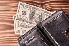 Rozpieczętowany portfel z amerykańskimi dolarami na drewnianym stole zdjęcia stock