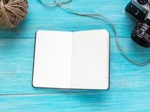 Rozpieczętowany pusty notatnik na błękitnym drewnianym podławym tle z starą kamerą i skein nić Mockup shalna obrazy royalty free