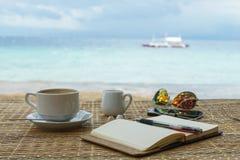 Rozpieczętowany pusty notepad jest na stole z okularami przeciwsłonecznymi, telefonem, hełmofonami i filipińskim, przy tłem tropi Zdjęcia Stock