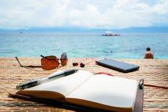 Rozpieczętowany pusty notepad jest na stole z okularami przeciwsłonecznymi, telefonem i hełmofonami, przy tropikalnym dennym tłem Zdjęcia Royalty Free