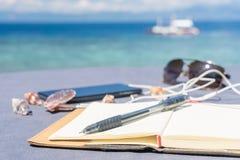 Rozpieczętowany pusty notepad jest na stole z telefonem i hełmofonami przy tropikalnym dennym tłem Obrazy Stock