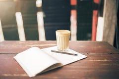 Rozpieczętowany pusty notepad, pióro i filiżanka kawy na drewnianym stole, Zdjęcie Royalty Free