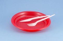 Rozporządzalny plastikowy czerwień talerz na błękitnym tle fotografia royalty free