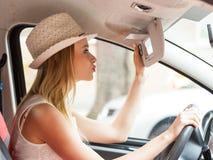Rozpraszająca uwagę kobieta jedzie jej samochód patrzeje w lustrze obraz stock
