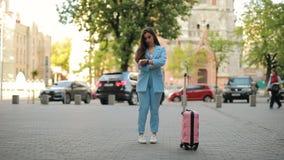 Rozpraszający uwagę zapominalski kobiety czekania taxi w mieście i zapomina walizkę zdjęcie wideo