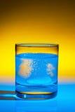 rozpuszcza pastylki szklaną wodę Fotografia Royalty Free
