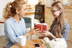 Rozradowana nastoletnia dziewczyna dostaje ona prezent urodzinowego fotografia royalty free