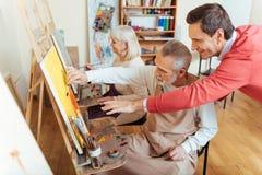 Rozradowanego artysty starszych osob pomaga mężczyzna w obrazu studiu zdjęcia stock