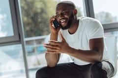 Rozradowany młody afro amerykański mężczyzna opowiada na smartphone Zdjęcie Royalty Free