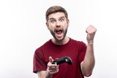 Rozradowany młody człowiek odświętności zwycięstwo w wideo grą fotografia royalty free