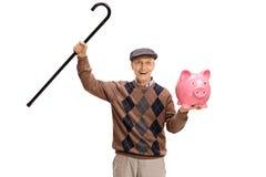 Rozradowany senior z chodzącą trzciną i piggybank Zdjęcie Stock