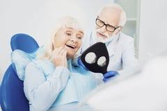 Rozrosła starsza kobieta dokładnie badać jej zęby obraz royalty free