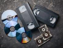 Rozrywki i środków technologia od 90's CD& x27; s, audio kasety, wideo kasety na czarnej betonowej powierzchni Obraz Stock