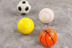 Rozrzuceni cztery koszykówki, baseballa, tenisa i piłki nożnej nowe miękkie gumowe piłki zdjęcie stock