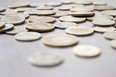 Rozrzucone monety na popielatym stole fotografia stock