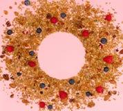 Rozrzucony granola, dokrętki i jagody na różowym tle, fotografia stock