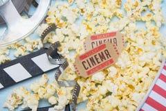 rozrzucony popkorn na błękitnym tle, filmu i dwa biletach, fotografia stock