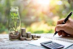 Rozsady w szklanym słoju, pieniądze monety sterty kierownika writing narastający biznesowy Męski plan biznesowy przy miejscem pra obraz stock