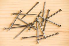 Rozsypisko żelazni gwoździe na drewnianej podłoga Obraz Royalty Free
