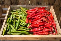 Rozsypisko chili pieprz, gorąca czerwień i zieleni pieprze na drewnianym bo, obrazy stock