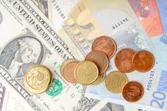 Rozsypisko monety na tle różnorodny euro i Dolarowi banknoty obrazy stock