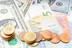 Rozsypisko monety na tle różnorodny euro i Dolarowi banknoty obrazy royalty free