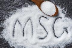 Rozsypisko monosodium glutamate na drewnianym łyżki i zmroku tle - teksta MSG obraz royalty free