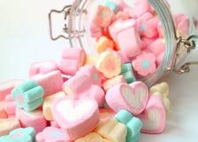 Rozsypisko Pastelowego koloru serce Kształtujący i kwiaty Kształtujący Marshmallow cukierki Rozpraszający od Szklanego słoju na b obrazy stock