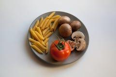Rozsypisko penne rigate makaron, brown szampiniony i pomidor na talerzu, obrazy stock