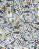 Rozsypisko pieniądze w sto dolarowych banknotach rozprzestrzenia na powierzchni Zdjęcia Stock