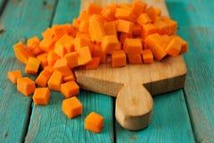 Rozsypisko pomarańczowi słodcy dyniowi sześciany na drewnianej desce na turkusie Zdjęcia Royalty Free