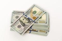 Rozsypisko sto dolarowych banknotów na biel powierzchni Zdjęcia Royalty Free