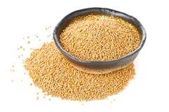 Rozsypisko surowi, nieprzerobeni musztardy ziarna nasiona w pucharze na bielu, Zdjęcie Royalty Free