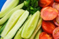 Rozsypisko wiele pomidoru i ogórka cięcia Obrazy Stock